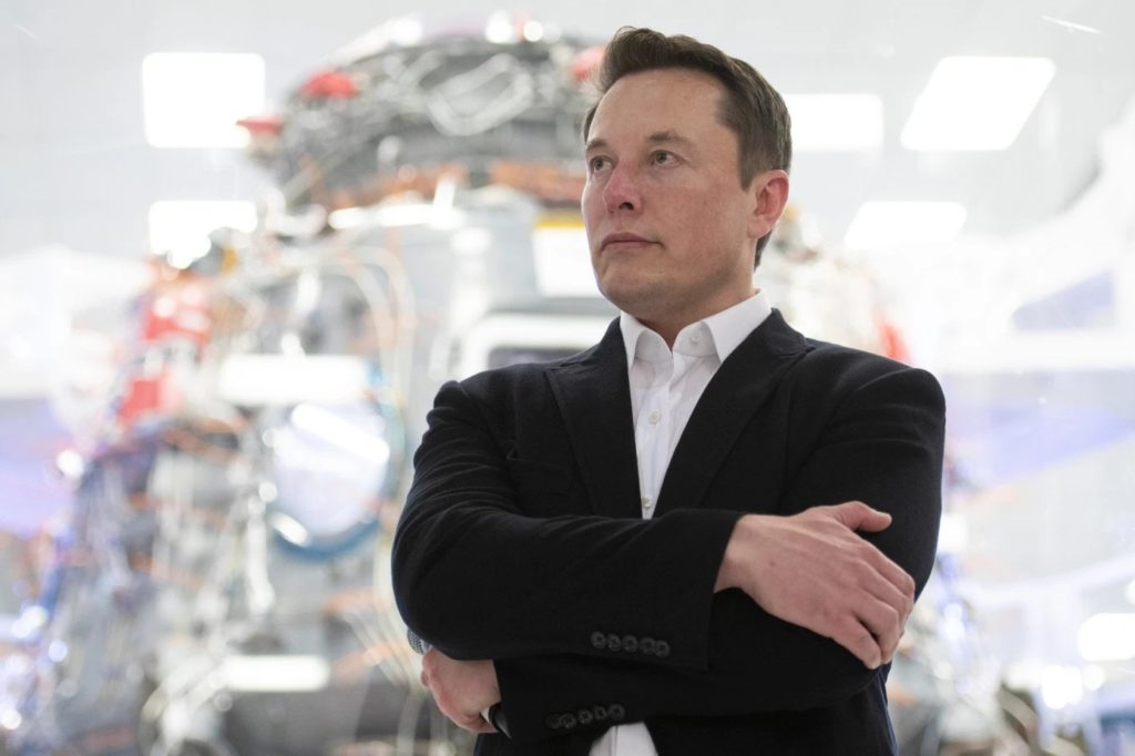 Photo of Elon Musk standing in a white shirt, black jacket, with his arms folded